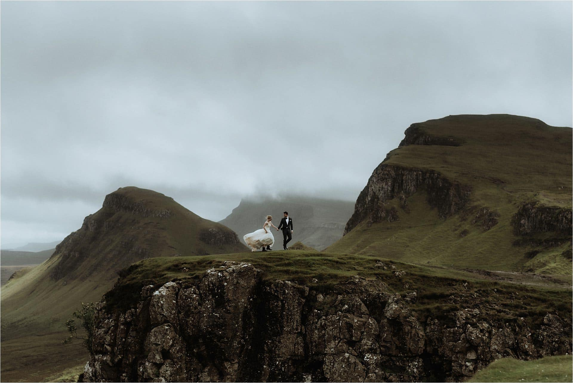 elopement couple walking in the rain on the Quiraing mountains on skye