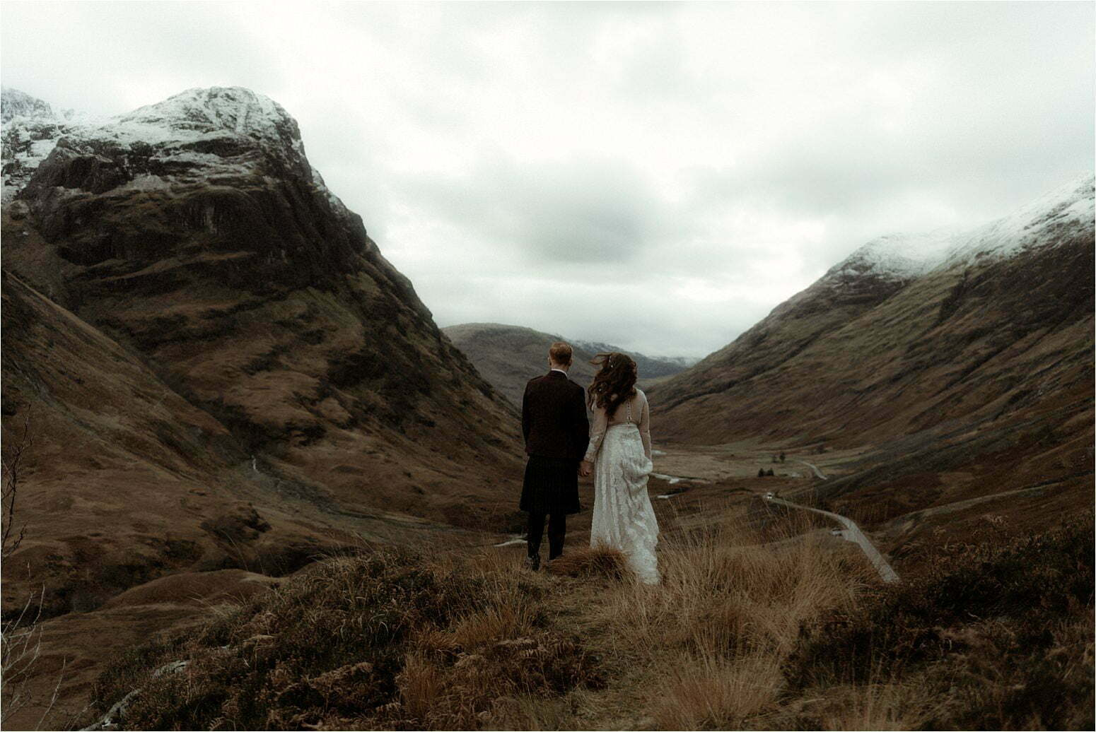 bride and groom standing in the mountains of scotland