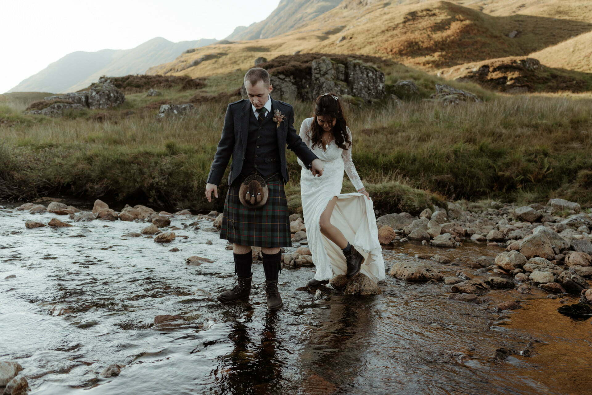couple walking in a river in glencoe