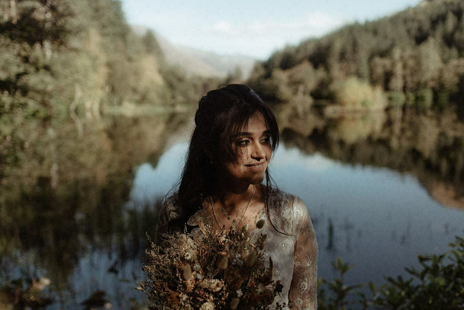 Indian bride during her elopement in scotland standing by glencoe lochan