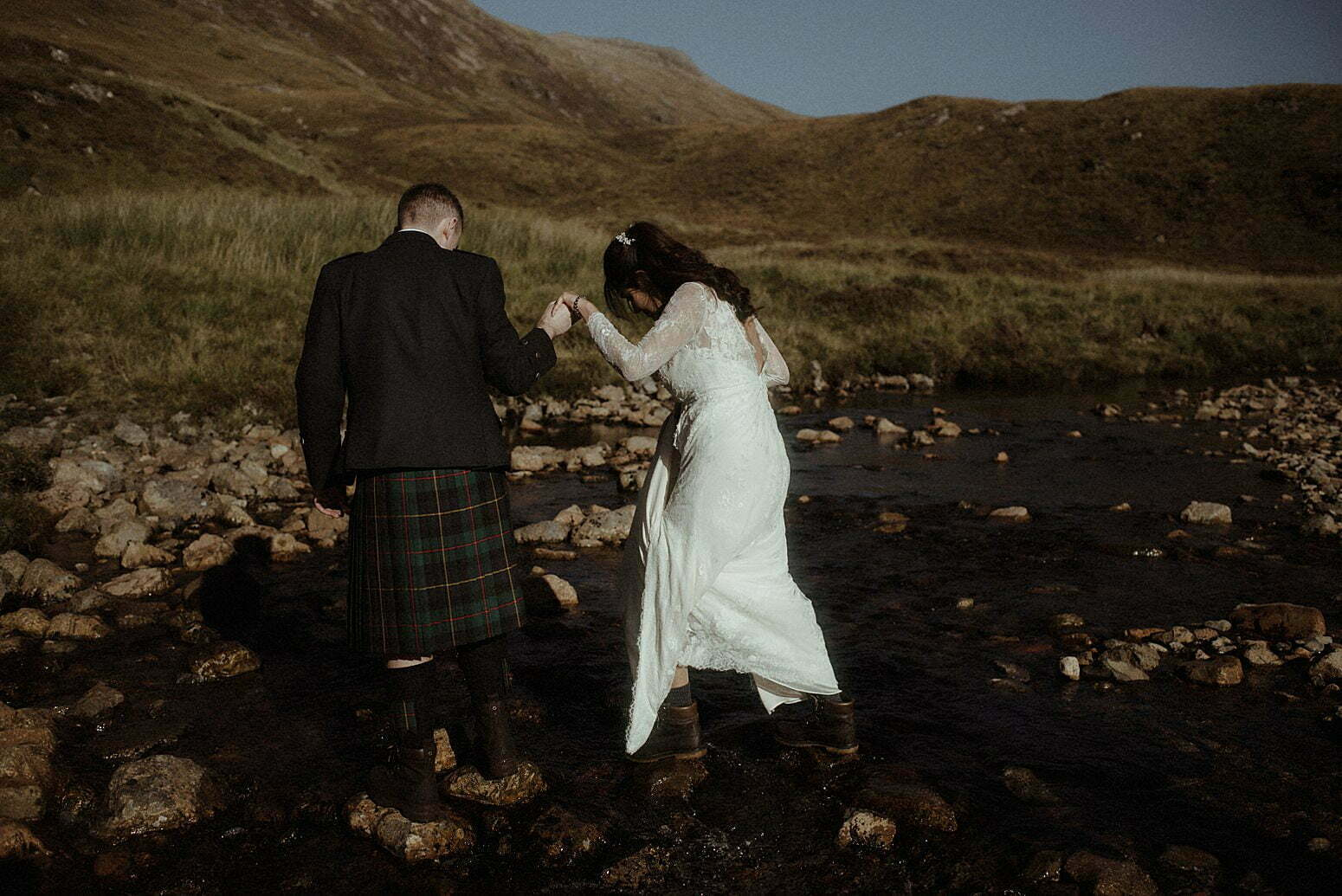 couple crossing a river in Glencoe during their autumn elopement in scotland