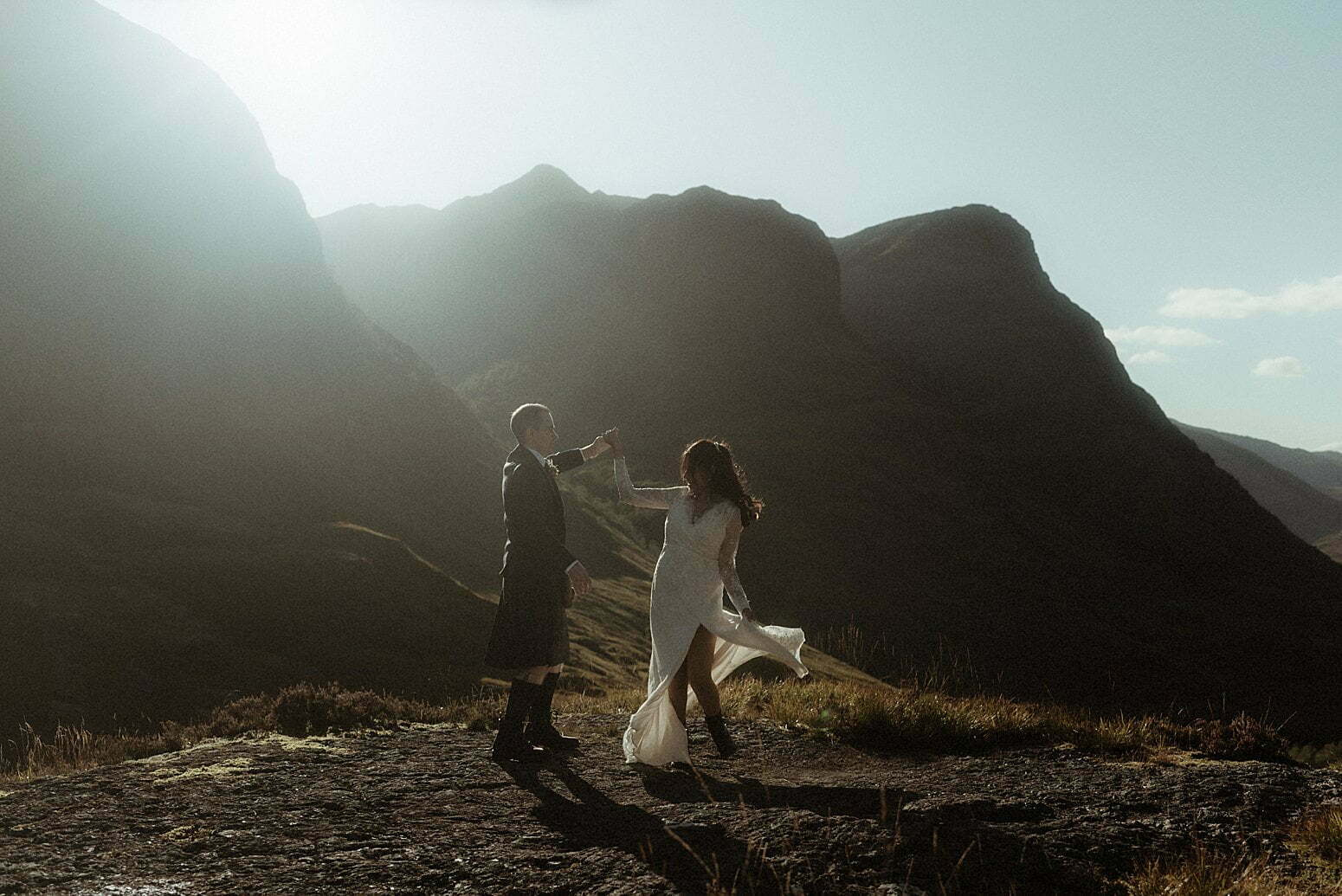 a bride and groom dancing in the mountains of Glencoe after their elopement in Scotland
