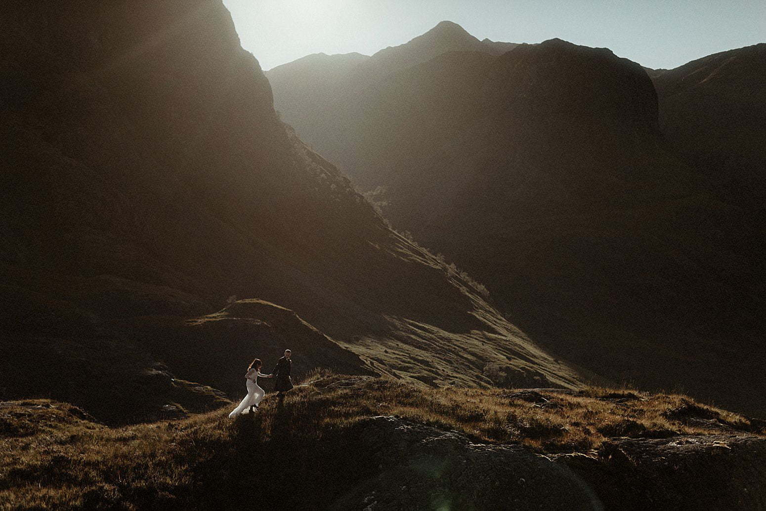 A couple walking in the sunlight between the mountains of Glencoe after their elopement in Scotland