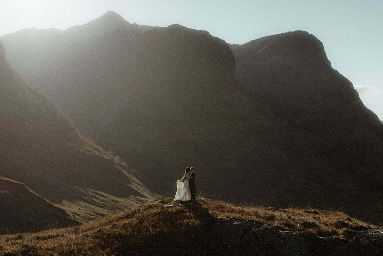 A couple dancing in the sunlight between the mountains of Glencoe after their elopement in Scotland