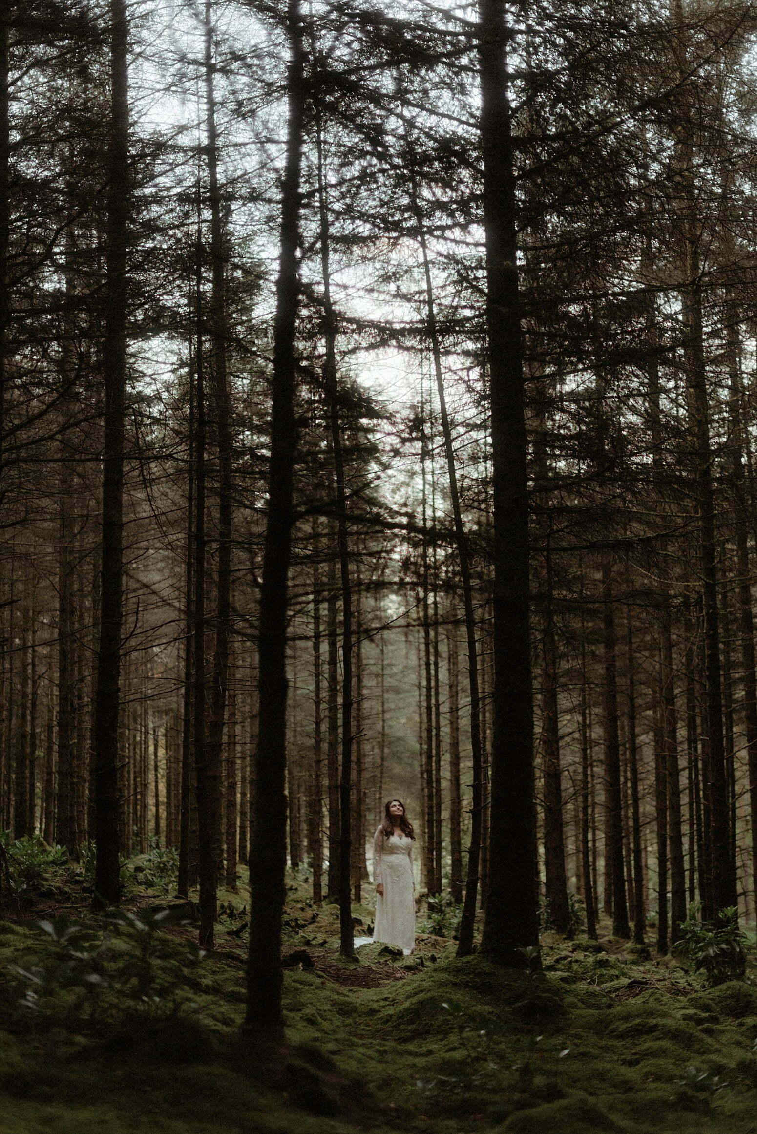 beautiful Bride walking in Woodland in Glencoe after her Scottish elopement