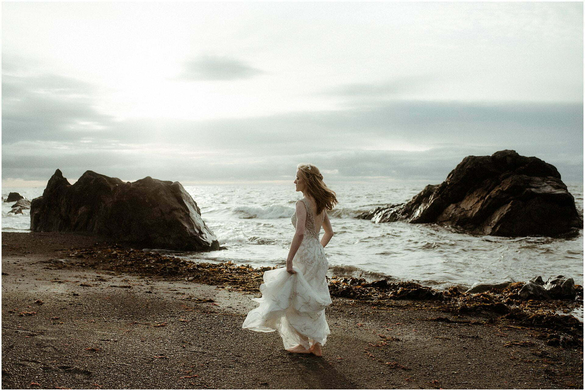 bride standing on a beach in Scotland during a Scottish elopement at sunset